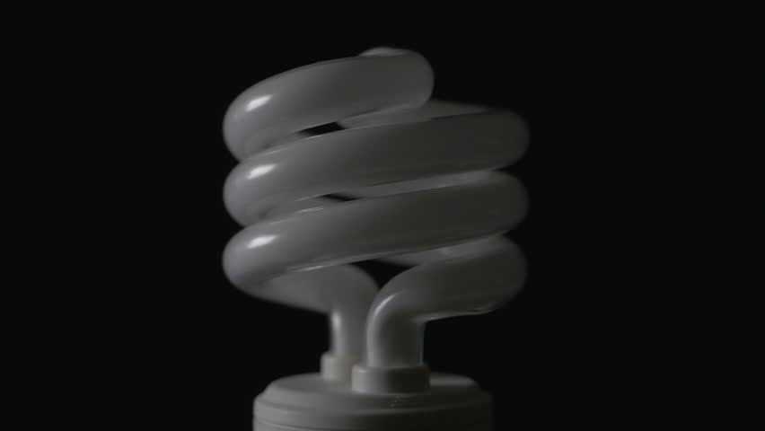 CFL light bulb being turned on black background.