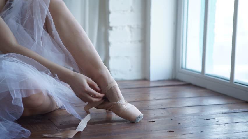 Ballet dancer tying slippers around her ankle woman ballerina pointe