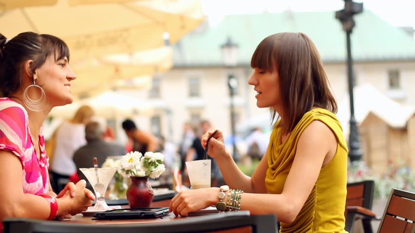 Two female friends chatting in restaurant, outdoors, camera stabilizer shot