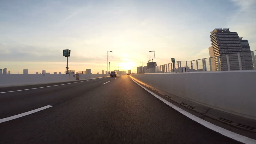 Driver's point of view across the bridge towards the climbing sunshine over the city horizon. Part 3. Eastbound over the Rainbow Bridge towards Daiba.