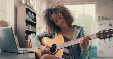 Attractive curly haired mixed race young girl sitting on wooden chair at a window wearing a grey hoodie concentrating focused learning to play guitar using laptop computer at home
