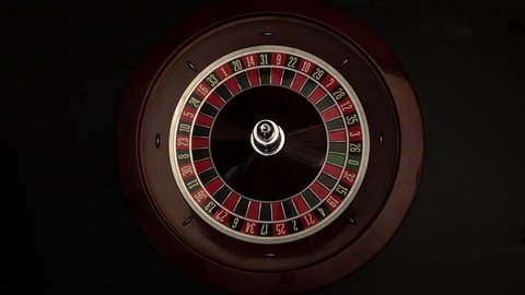 Person spinning roulette on black