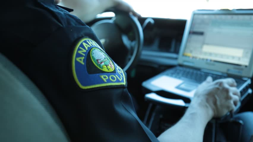 Anaheim, CA., January 2016: Policeman sitting in the driver's seat of his patrol car looking at a laptop