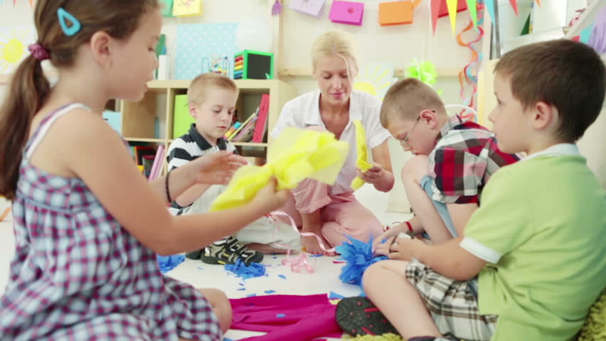 Group Of Preschoolers Making Paper Flowers With Their Teacher