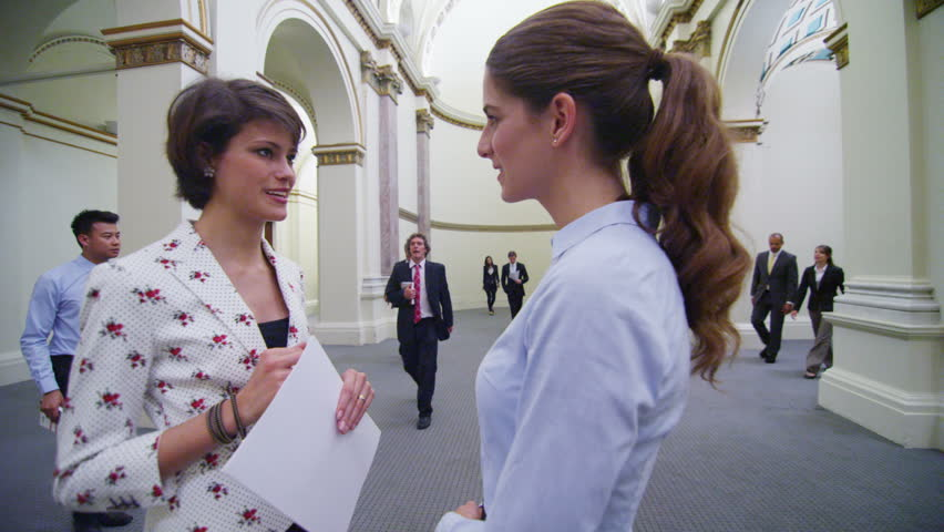 Diverse group of business or political delegates meeting in an elegant, classically designed building. Two attractive young businesswomen stand and chat together with others. In slow motion.   Shutterstock HD Video #14100986