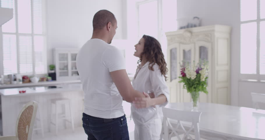 4k / Ultra HD version Happy and attractive young couple in love dance together in their stylish apartment. In slow motion. Shot on RED Epic | Shutterstock HD Video #14103386