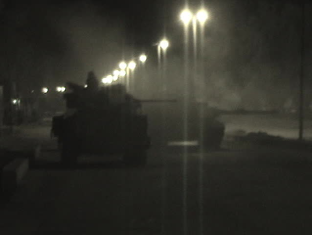 An Abrams tank fires into an Iraqi village.