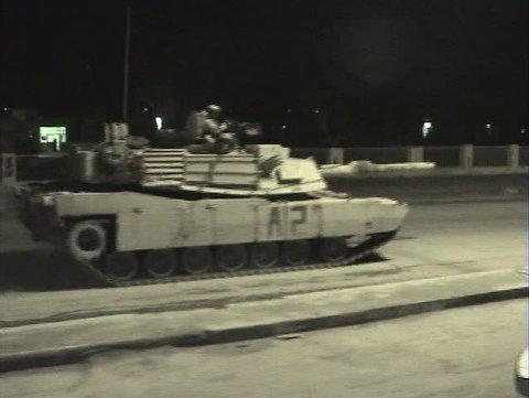 Abrams tanks speed through streets in Iraq.