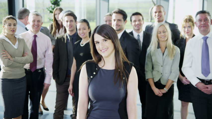 4k / Ultra HD version Portrait of a beautiful young businesswoman who is standing in front of the rest of her business team. They all look into the camera and smile. In slow motion. Shot on RED Epic   Shutterstock HD Video #14127446