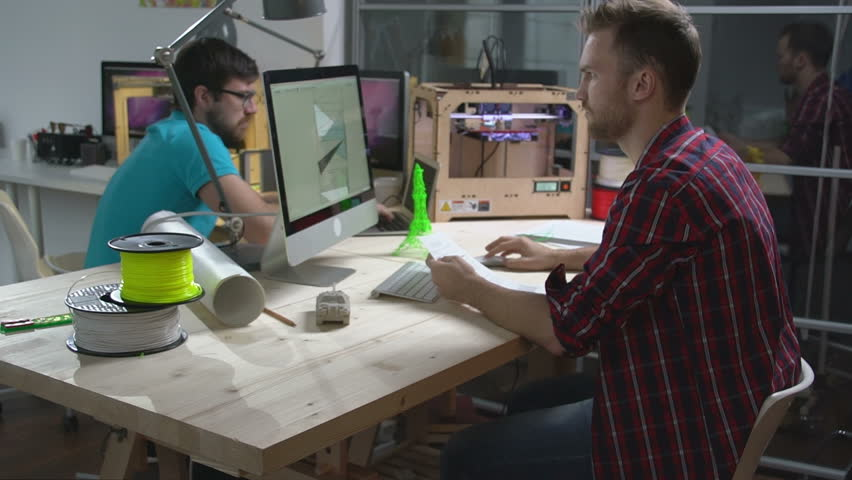 Two young men creating 3d models with computer software and printing them on 3D printer at small design studio