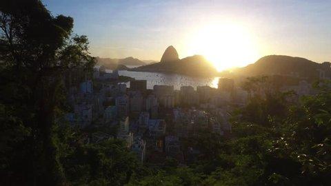 Avião de linha aérea comercial entrando no enquadramento para aterrissar na cidade maravilhosa do Rio de janeiro, ao fundo sol nascendo no cartão postal Carioca, o Pão de Açucar na Baia de botafogo.