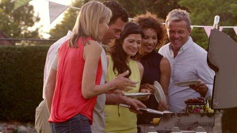 Mature Friends Enjoying Outdoor Barbeque Shot On R3D