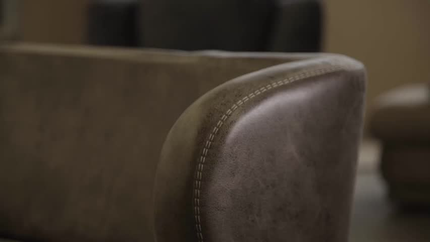 Man check stitches on a sofa in furniture factory