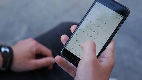 Close-up male hands scrolling screen on smartphone. Person using calendar app on the mobile device.