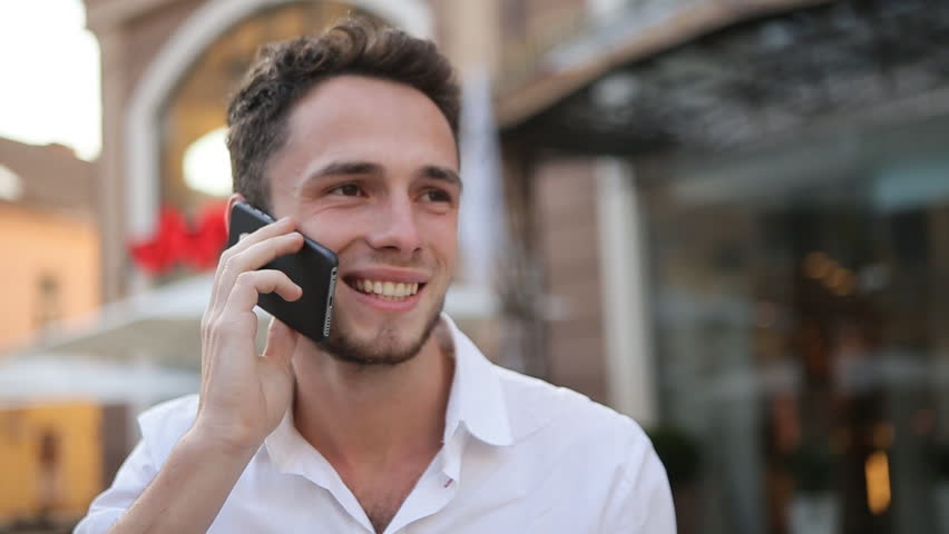 Young male holding on the phone, smiling and touching his neck.   Shutterstock HD Video #14238110