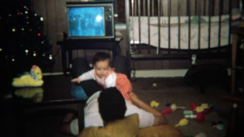 BOULDER, COLORADO 1971: Baby crawls on dad while watching tv laying on floor.