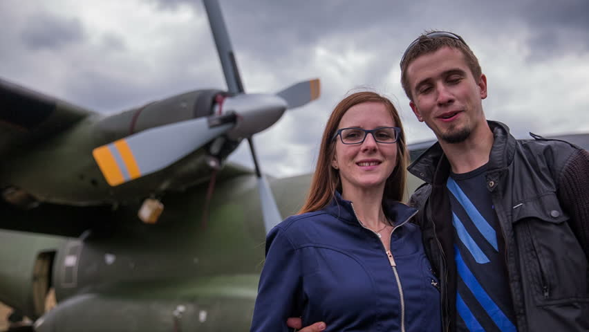 Couple take selfie photo in front of big army aircraft. Young man and woman stand in front of an aircraft with big propellers on a wing. Smiling in camera. Portrait shot.