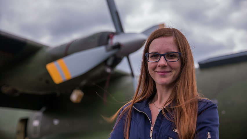 Woman portrait in front of an old aircraft. Young beautiful woman with stylish army jacket stand in front of older bomber aircraft with a propeller in background.