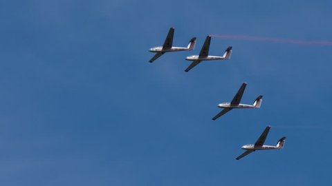 Sailplanes gliding under blue sky. Air show presentation of four sailplanes flying high in the sky without any propellers.