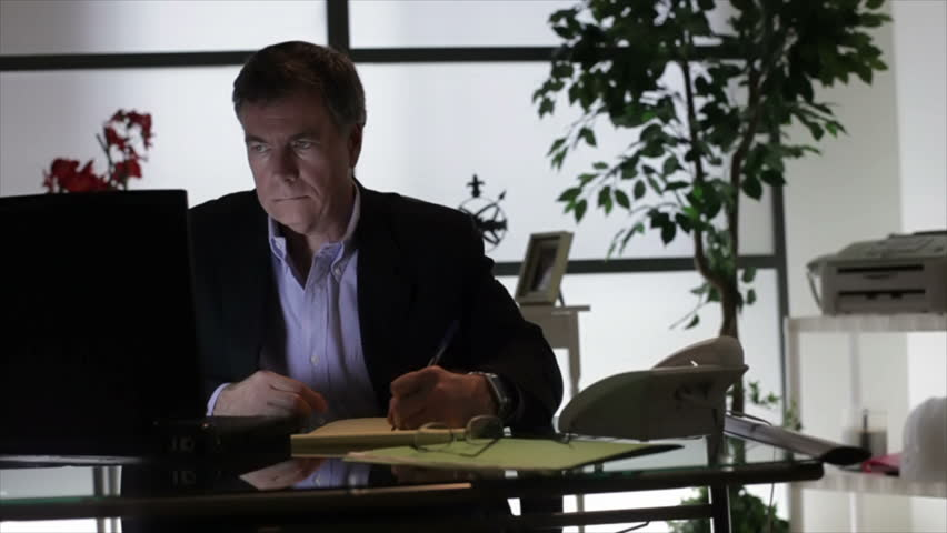 A businessman sitting in his dimly lit office writing something on a tablet from information he has on his laptop.
