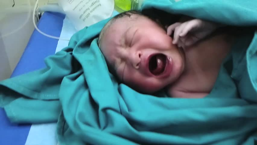 Newborn baby crying at delivery room.
