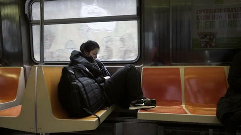 NEW YORK - JAN 25, 2016: girl sitting alone sleeping or reading on subway B train, graffiti in window, winter NYC. Transportation is different for millennials than it was for their parents.