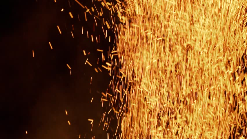 Lot of sparks from large bonfire in the night in slow motion. Beautiful abstract background on the theme of fire, light and life.