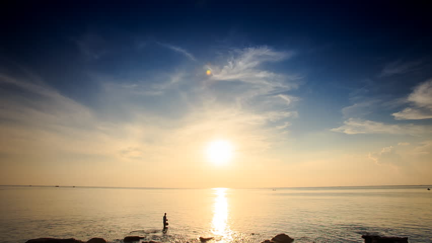 Man's silhouette in shallow sea by beach against bright sun on skyline sun path reflection at sunset | Shutterstock HD Video #14323426