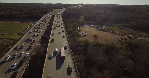 The camera moves above the north and south sides of Austin, Texas' Mopac highway during rush hour traffic.  The traffic moves slowly as cars are heading home from a long day at work.