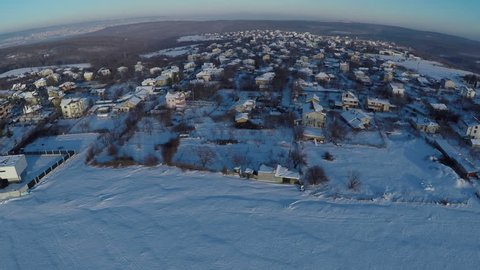 Aerial view, flight over houses in the winter countryside