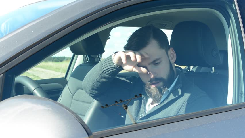 young handsome hipster man sits alone in the car in hot weather - sun is shining on him