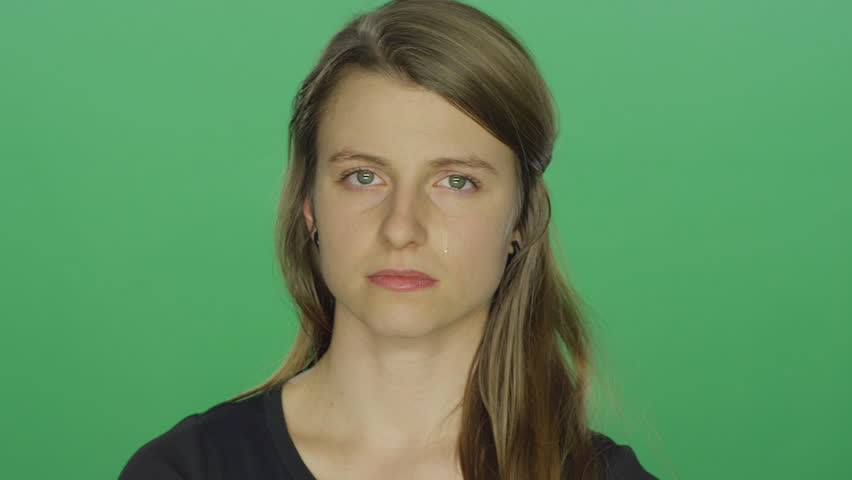 Young women looks sad and cries, on a green screen studio background | Shutterstock HD Video #14361316