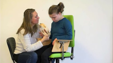 A disabled child in a wheelchair enjoying music therapy together with a special needs carer / Working together with disability