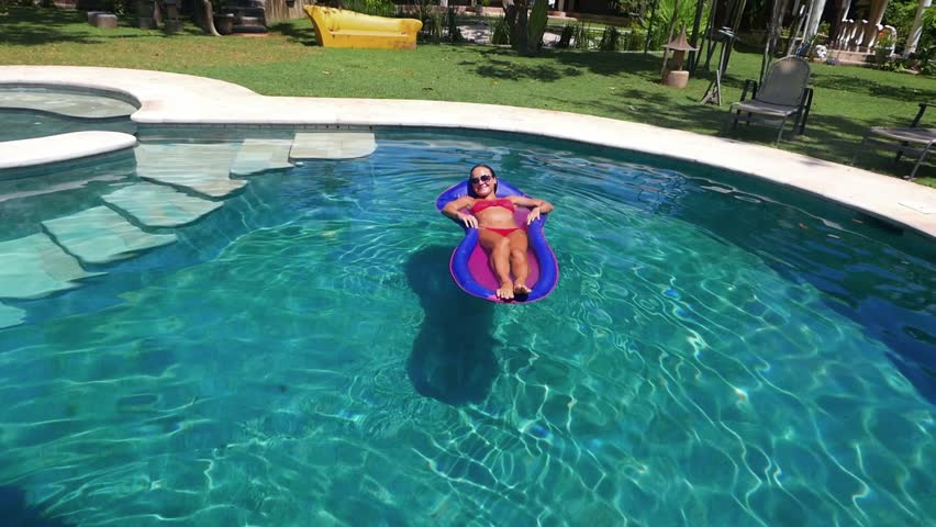 ... swimming pool Girl with a beautiful body is relaxing on an air mattress  in a pool. Dog Happy Young ... 3d0fcbfd4