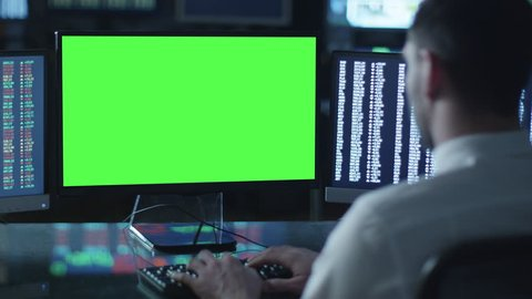 Man is working on a computer with mock-up green screen in a dark office filled with displays. Shot on RED Cinema Camera in 4K (UHD).