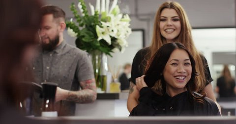A happy young woman after having her hair groomed at her local salon. Shot on RED Epic in slow motion.