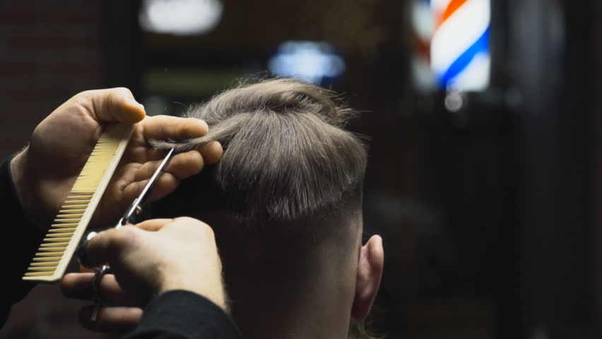 Barber cuts the hair of the client with scissors slow motion close up