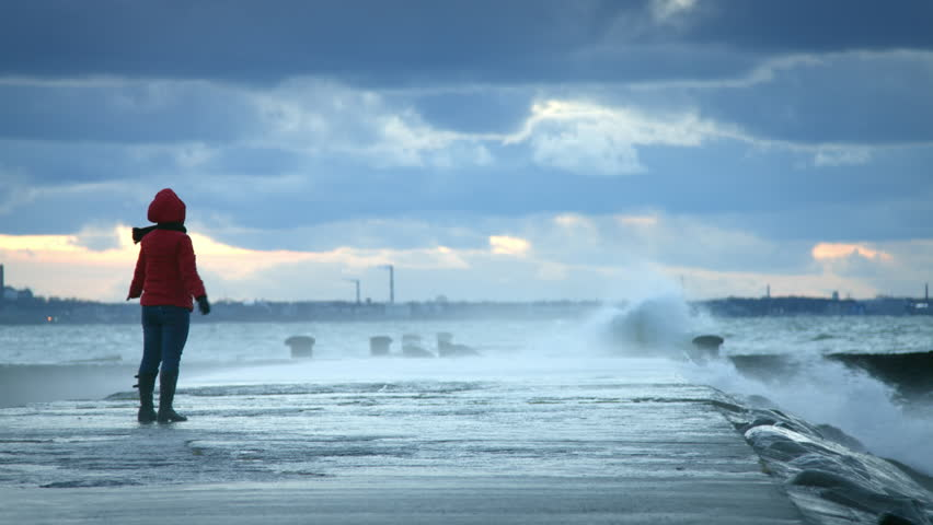 Woman standing near storm waves hitting the pier