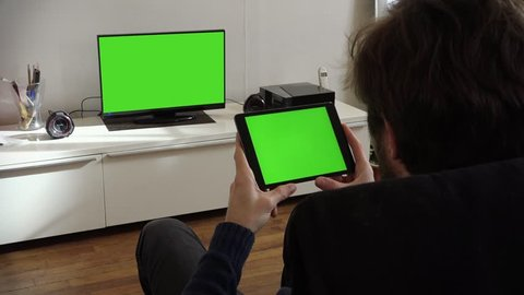 Man Holds Tablet And Watches Television Green Screen. Man holding tablet green screen and watching television green screen at home - 1080p
