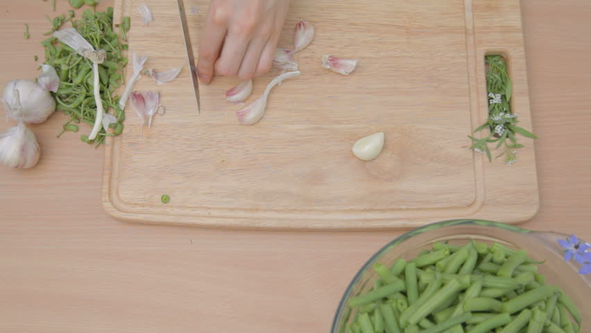 Cutting with knife garlic base and removing dry husks outdoors