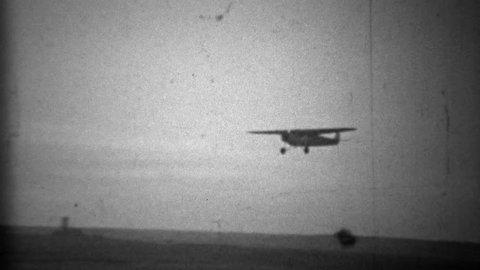 DENVER, COLORADO 1934: Propeller plane landing in primitive airport landing strip.