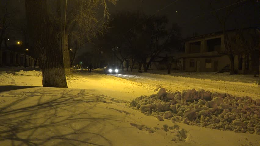 Snow-covered city street with night lights, is fine snow, in bad stormy weather, city, Central Europe