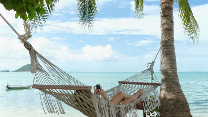 Woman Using Mobile Phone In A Hammock On The Beach Stock Footage Video  14566666 | Shutterstock - Woman Using Mobile Phone In A Hammock On The Beach Stock Footage