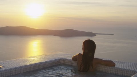 Luxury Spa Travel. Relaxing woman at the edge of swimming pool. Female is watching beautiful view of sunset. She is enjoying her vacation at resort by sea.