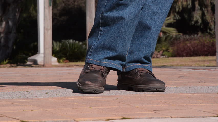 Man legs in brown working shoes do the pee dance. He needs to urinate so urgently. Shooting from the ground / shallow depth of field