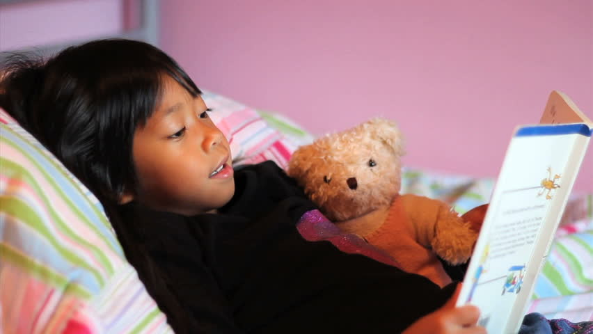 A cute little 5 year old Asian girl reads a story book to her teddy bear.