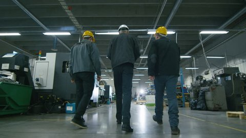 Back view of senior engineer and two workers are walking with papers through the factory space. Shot on RED Cinema Camera in 4K (UHD).