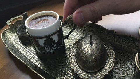 Woman is drinking Turkish coffee.