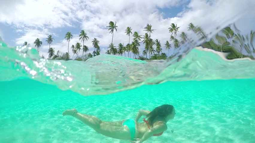 SLOW MOTION HALF UNDERWATER CLOSE UP: Happy young woman swimming and relaxing in stunning crystal clear lagoon on exotic island with white sandy beaches in French Polynesia