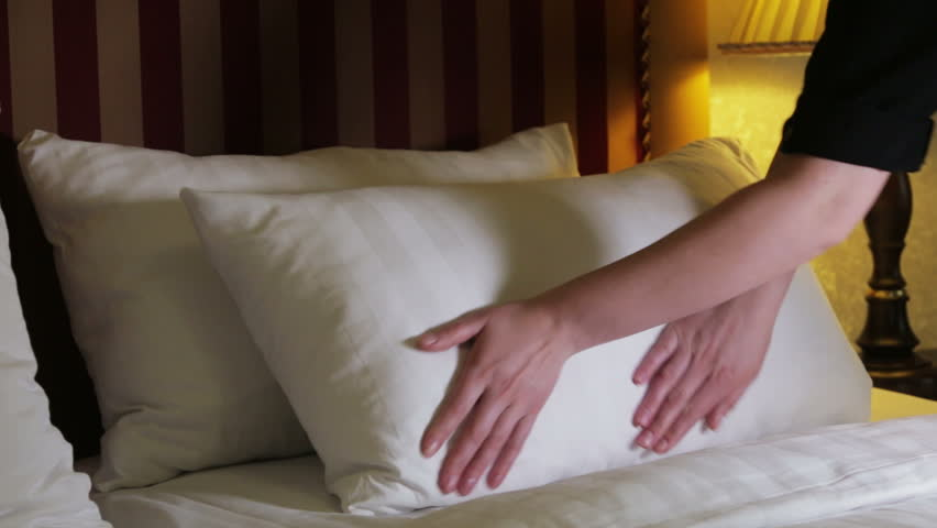 female hands fix bed linen on the bed close-up shot. the bed in the hotel. maid veiled bed linen on the bed.